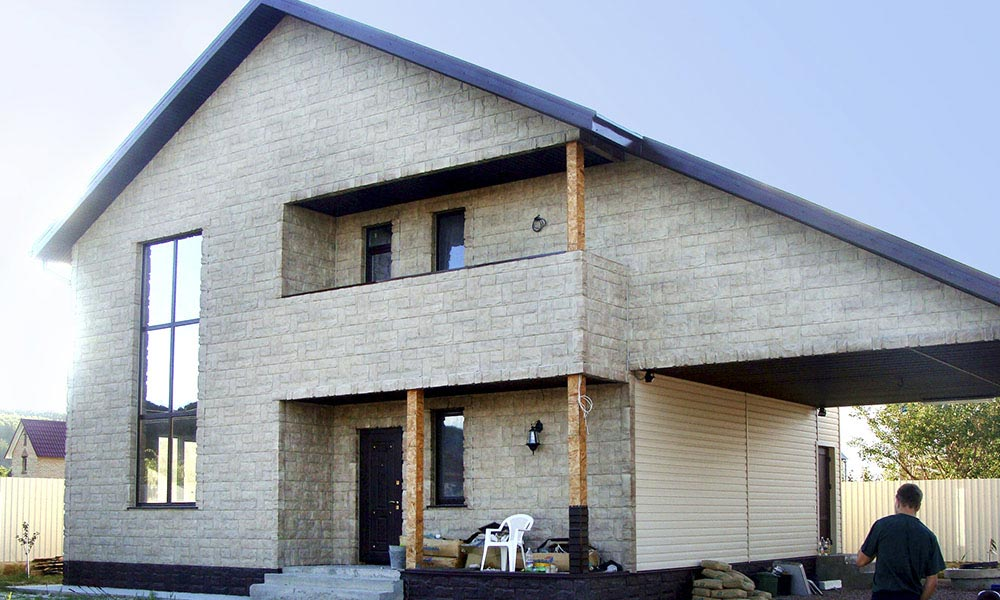 Фасад дома обшит садингом под Гранит