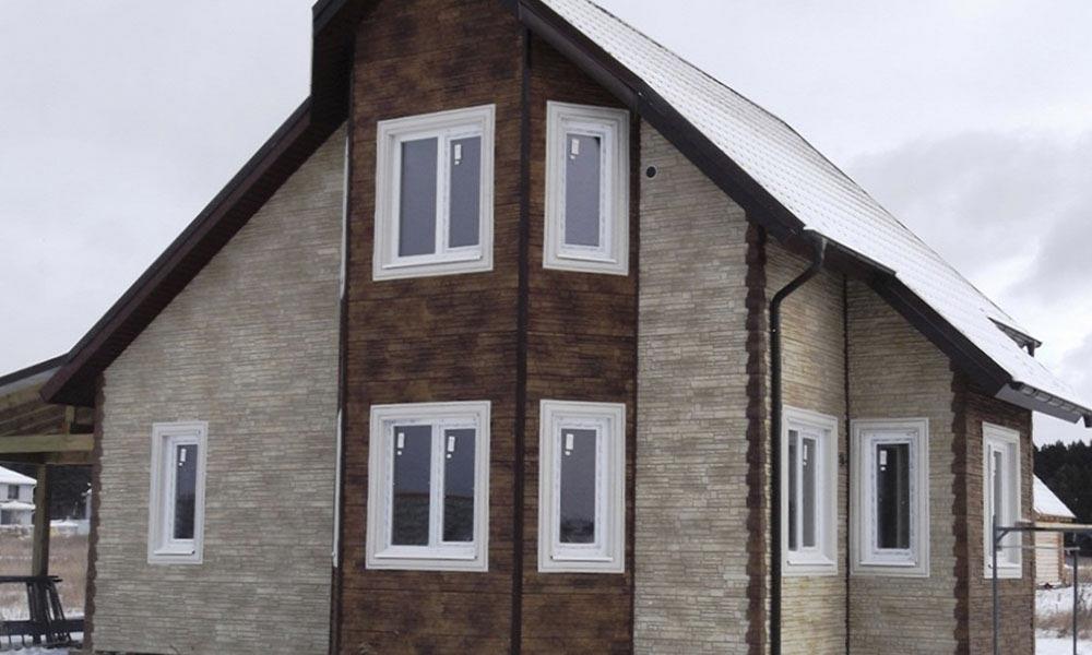 дом обшит фасадными панелями под скалистый камень