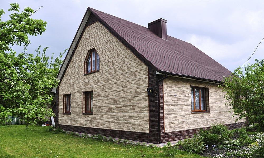 уютный домик обшит цокольным сайдингом под скалистый камень
