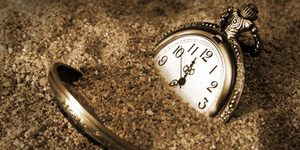 A pocket watch is buried in the dirty sand.